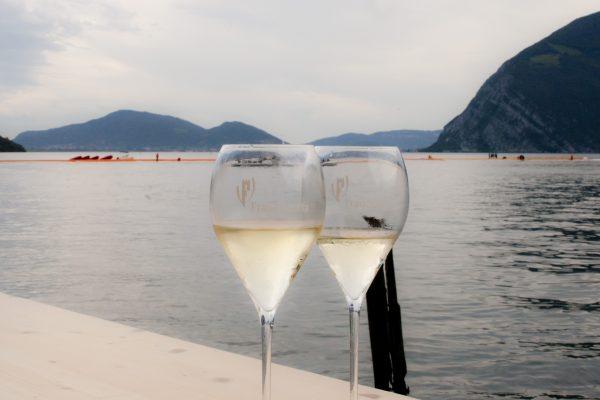 Due bicchieri di Franciacorta con lo sfondo del Floating Piers, l'opera dell'artista Christo a Iseo - Fonte: Ufficio stampa